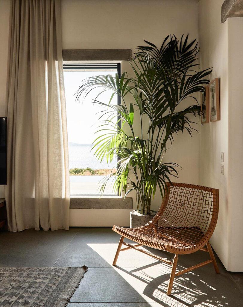 A rattan chair at Villa Mandra: A Summer Home In Mykonos, Greece.